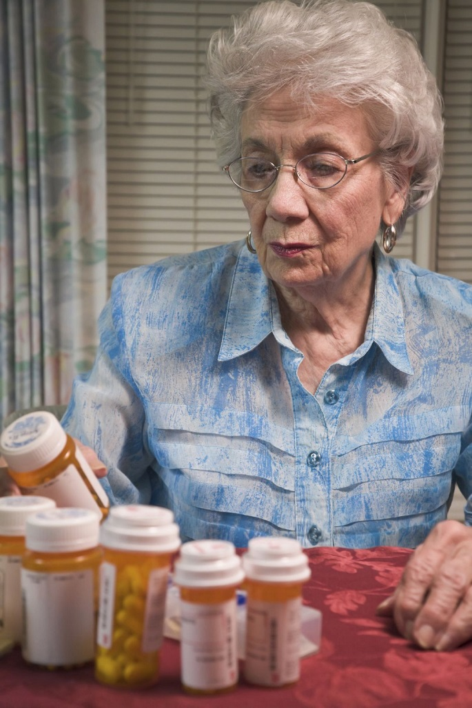 Senior woman reads prescription medication bottle. Focus on face.